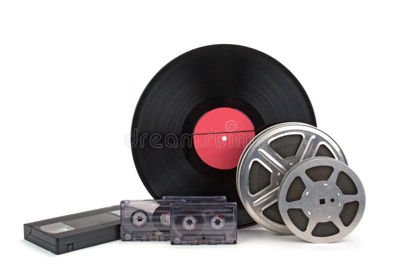 Rollo de película viejo con la tira, la película fotográfica, las grabaciones de audio y los discos de vinilo foto de archivo libre de regalías