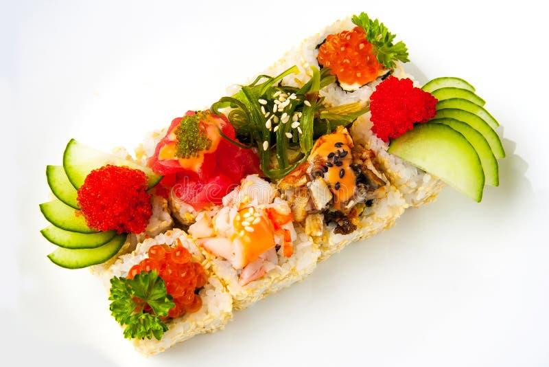 Rollo de sushi clasificado con las semillas de sésamo, pepino, tobiko, ensalada del chuka, anguila, atún, camarón, salmón imagen de archivo