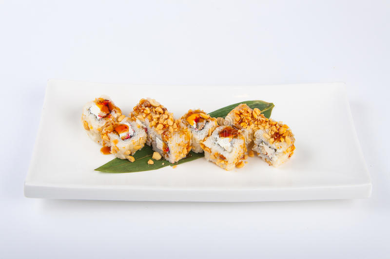 Rollo de sushi con el atún, queso de Philadelphia, caviar del pez volador, cacahuetes foto de archivo