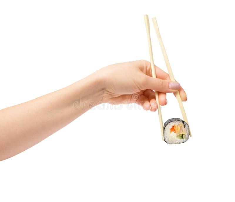 Rollo de sushi con los palillos de madera en mano femenina en blanco foto de archivo