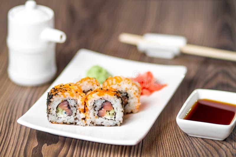 Rollo de sushi con los salmones, el wasabi y el jengibre fotos de archivo libres de regalías
