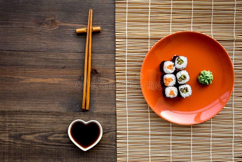 Rollo de sushi con los salmones y el aguacate en la placa con la salsa de soja, palillo, wasabi en la opinión superior del fondo  fotografía de archivo libre de regalías