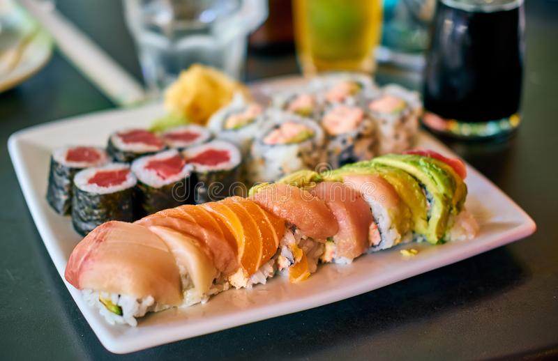 Rollo de sushi del arco iris en la tabla imagen de archivo
