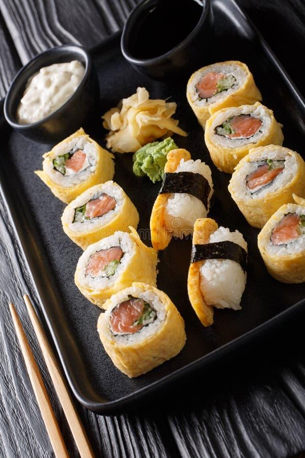 Rollo de sushi determinado del tamagoyaki con el primer del arroz, del queso, de los salmones y del aguacate en una placa vertica imagenes de archivo