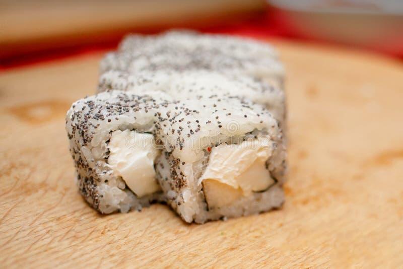 Rollo de sushi extraño con la amapola foto de archivo