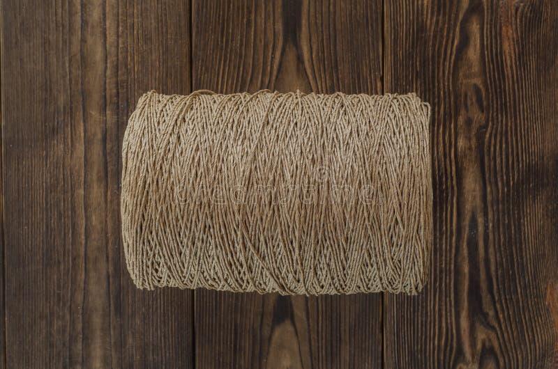Rollo de un yute de la guita en el fondo de madera imagen de archivo