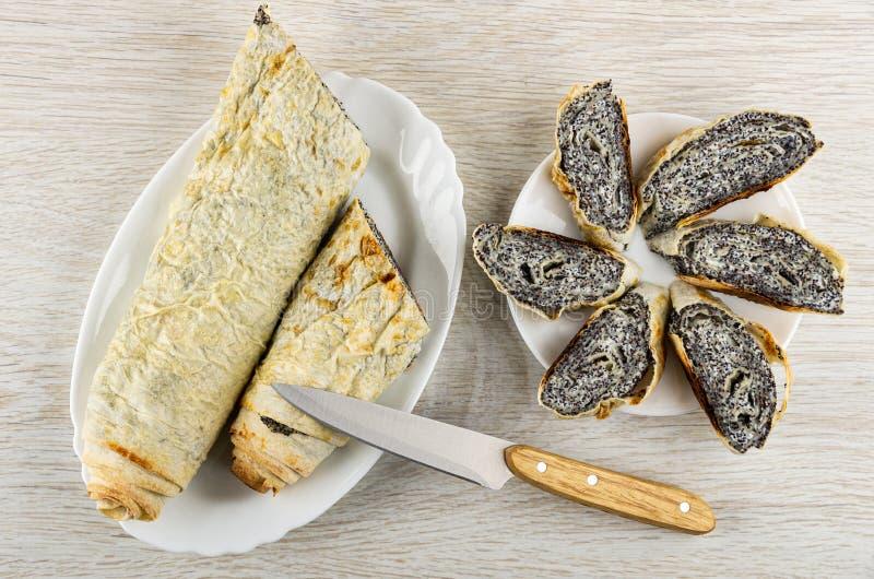 Rollo del pan Pita con el relleno del requesón, amapola en el plato, partes de rollos en la placa, cuchillo en la tabla Visi?n su imágenes de archivo libres de regalías