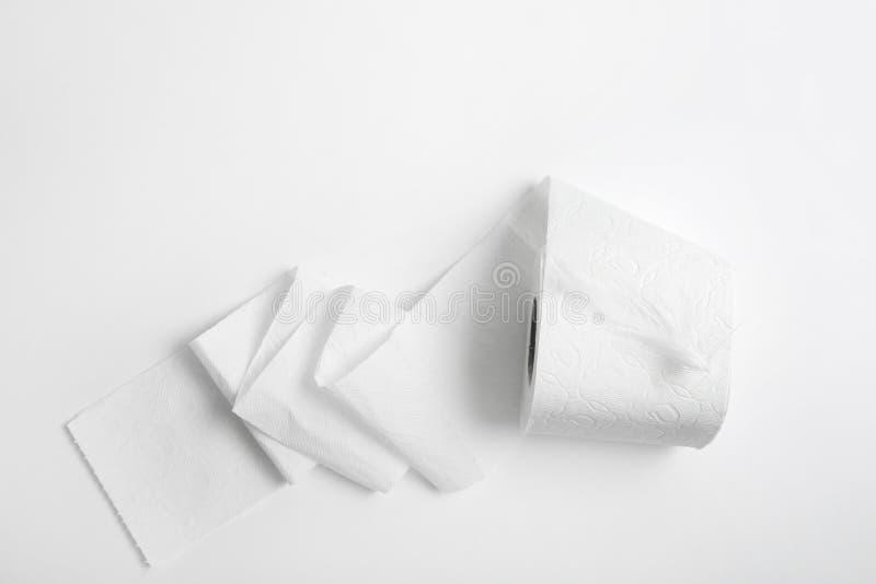 Rollo del papel higiénico con la pluma en el fondo blanco foto de archivo libre de regalías