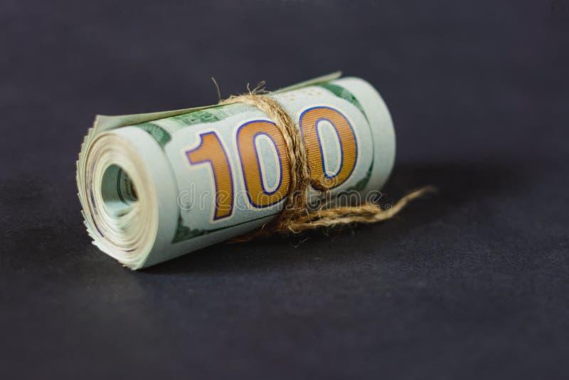 Rollo en la denominación de cientos dólares en un fondo oscuro fotos de archivo