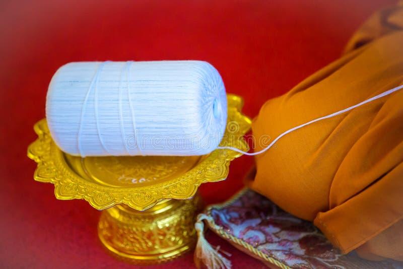 Rollo santo del hilo del foco en la bandeja del oro con el pedestal amuleto en ceremonia budista de la religión imagen para los o fotografía de archivo