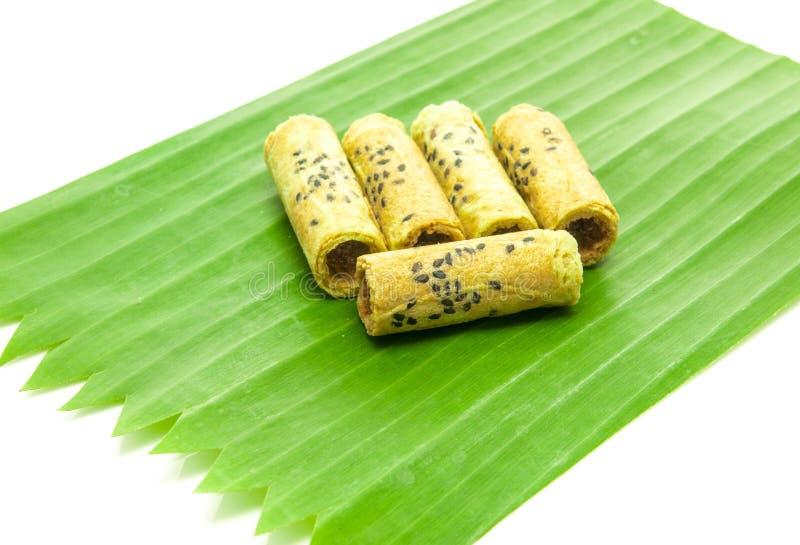 Rollo tailandés de la galleta del coco en la hoja del plátano fotos de archivo