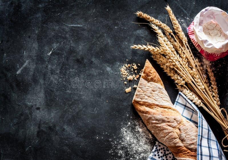 Rollo, trigo y harina de pan en fondo negro imagen de archivo