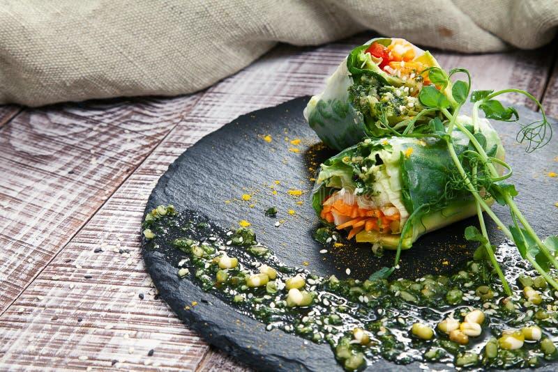 Rollo vegetariano fresco con las hierbas y las especias de las verduras en un tablero negro y un fondo de madera fotografía de archivo