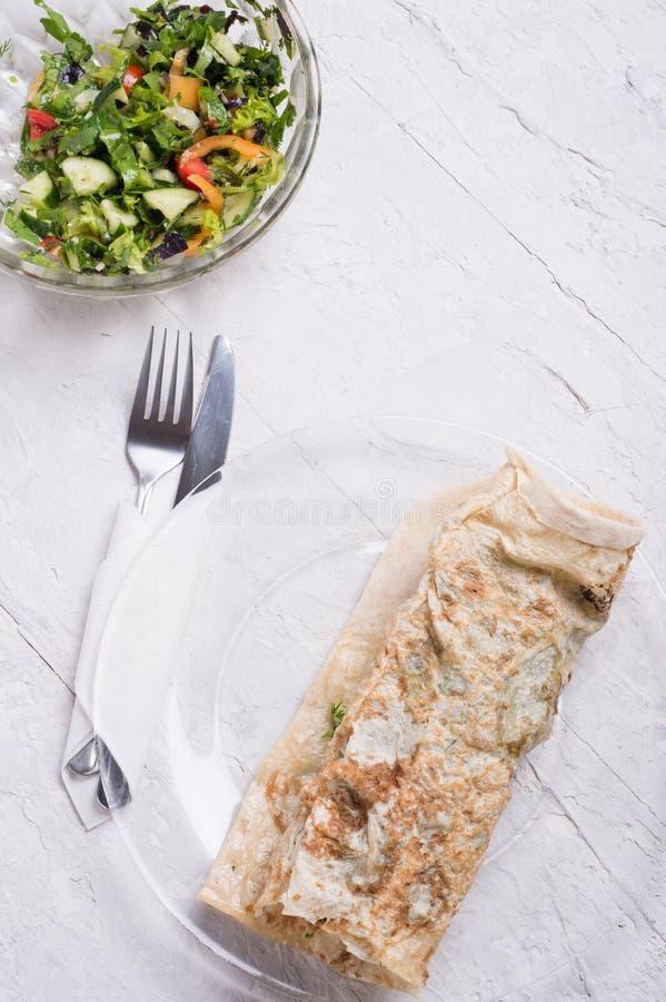 Rollo y ensalada vegetarianos del bocadillo del shawarma de cocinado servido en el estilo de Provence Alimentos de preparaci?n r? imagen de archivo