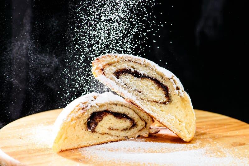 Rollos de canela recientemente cocidos asperjados con el azúcar en polvo en el wo imagen de archivo