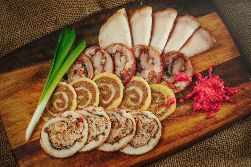 Rollos de carne deliciosos cortados en un fondo de madera con el rábano picante y las cebollas verdes, un servicio acogedor del r fotos de archivo libres de regalías