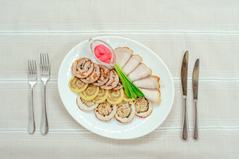Rollos de carne deliciosos cortados en una placa blanca con la cebolla del rábano picante y de la primavera, servicio del restaur foto de archivo libre de regalías