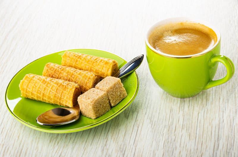 Rollos de la oblea, cuchara, azúcar en el platillo, taza verde con café en la tabla de madera imágenes de archivo libres de regalías