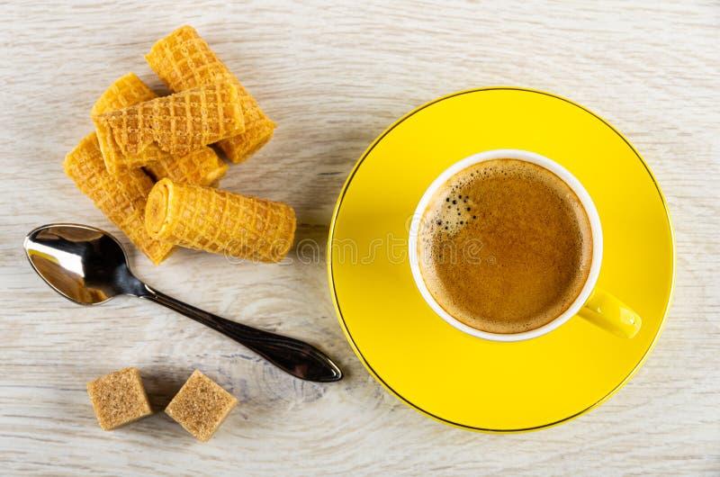Rollos de la oblea, cuchara, azúcar, taza amarilla con café en el platillo en la tabla de madera Visi?n superior imagen de archivo