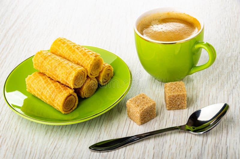 Rollos de la oblea en el platillo, cuchara, azúcar, taza verde con café en la tabla de madera foto de archivo