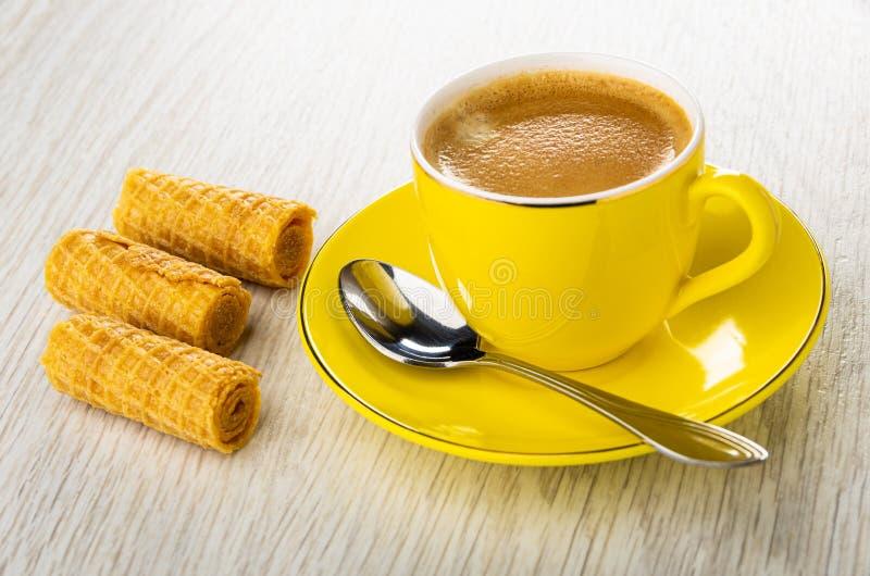 Rollos de la oblea, taza amarilla con el café, cuchara en el platillo en la tabla de madera imagen de archivo libre de regalías