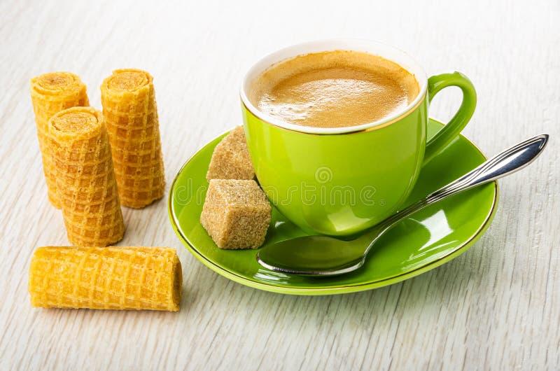 Rollos de la oblea, taza verde con el café, cuchara, azúcar en el platillo en la tabla de madera fotos de archivo