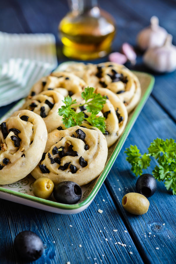 Rollos de pan cocidos con las aceitunas y el ajo imagen de archivo