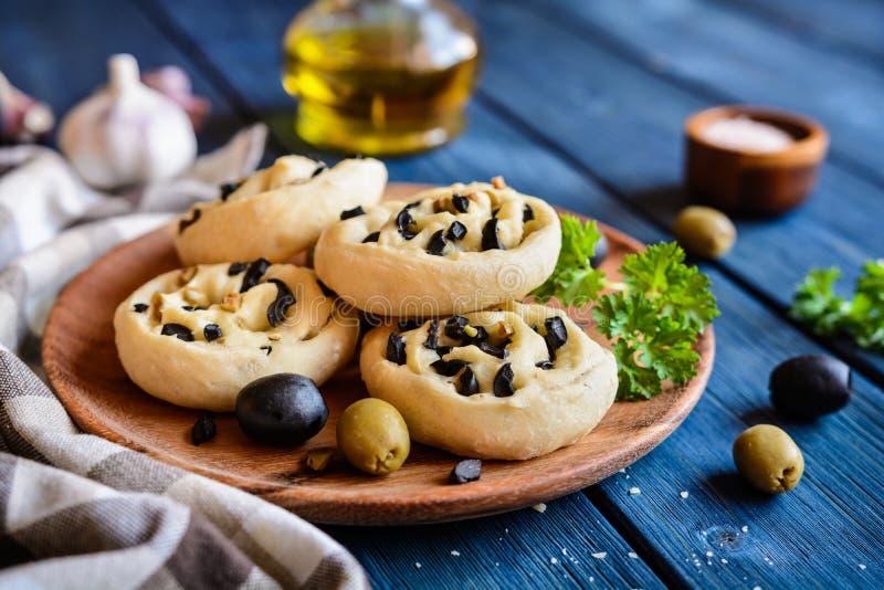Rollos de pan cocidos con las aceitunas y el ajo imagenes de archivo