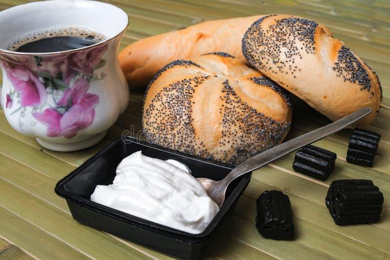 Rollos de pan con semillas de amapola y una taza de café foto de archivo libre de regalías