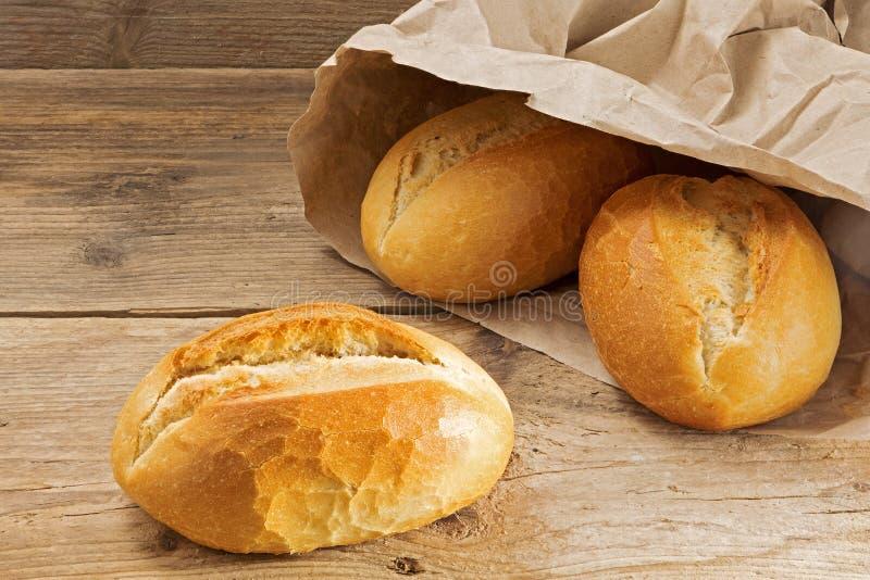Rollos de pan en una bolsa de papel en una tabla de madera rústica imagen de archivo libre de regalías