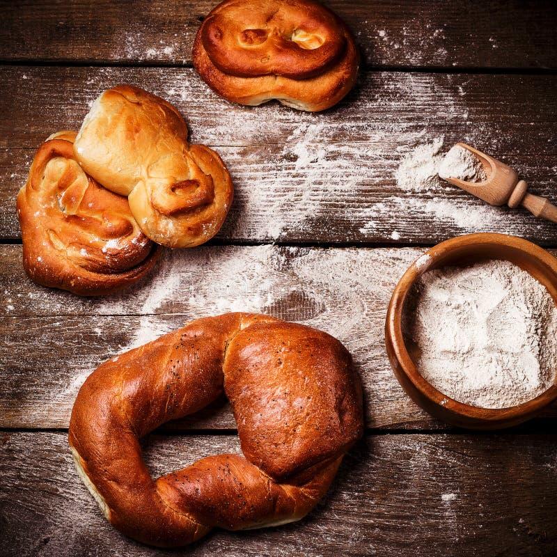 Rollos de pan recientemente cocidos en la tabla de madera vieja fotografía de archivo