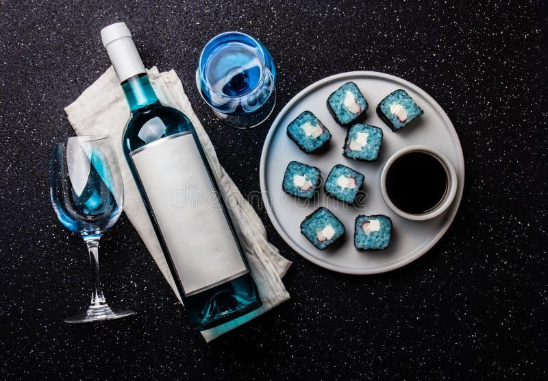 Rollos de sushi azules y vino azul Chardonnay en fondo negro Vino azul español, bebida de moda, vino de lujo, visión superior fotografía de archivo libre de regalías