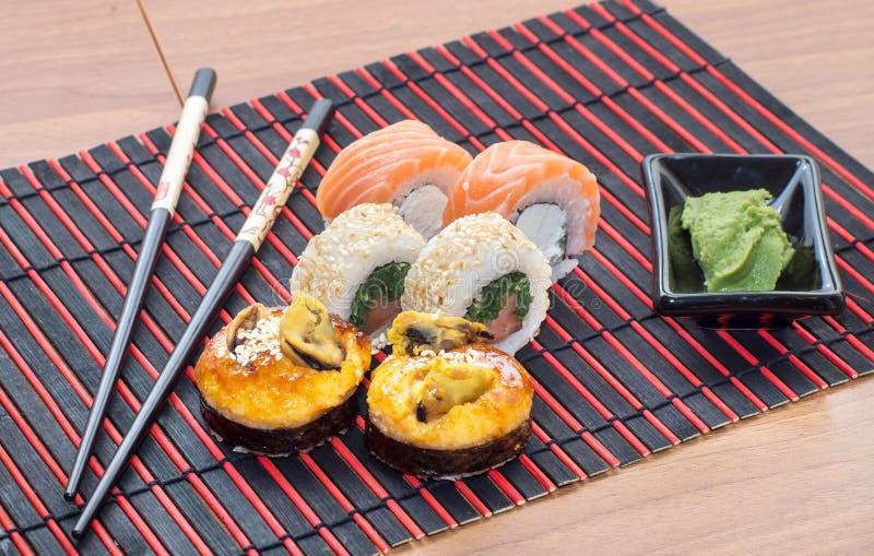 Rollos de sushi con los palillos fotos de archivo