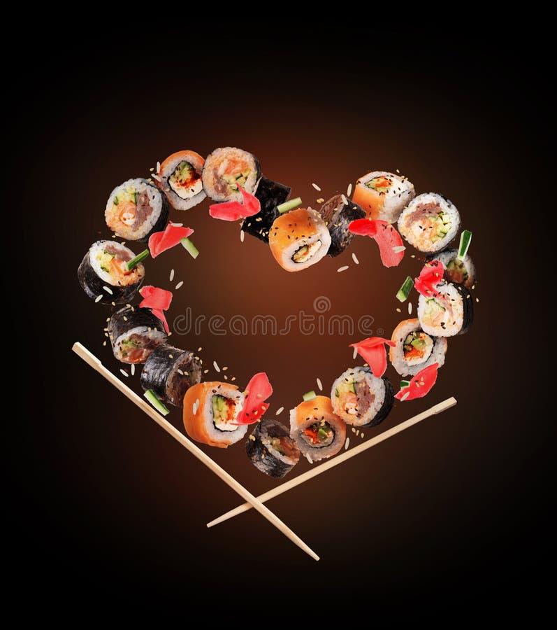 Rollos de sushi con los palillos congelados en el aire en la forma del corazón, en fondo negro fotos de archivo libres de regalías