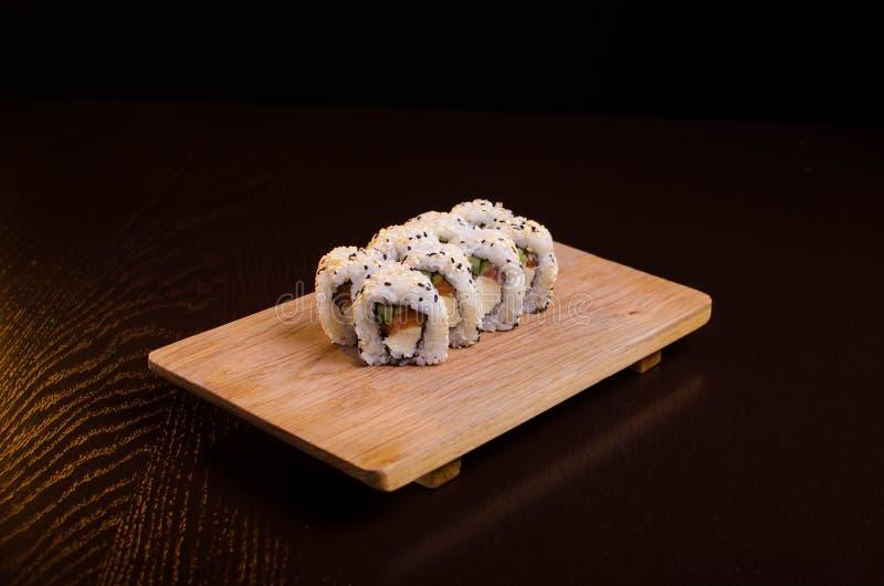 Rollos de sushi con los salmones y el queso Cocina tradicional japonesa Arroz con los mariscos El maki del menú rueda en un fondo foto de archivo libre de regalías