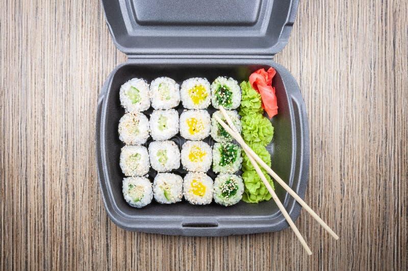 Rollos de sushi en un envase en una tabla de madera Visión superior imagen de archivo libre de regalías