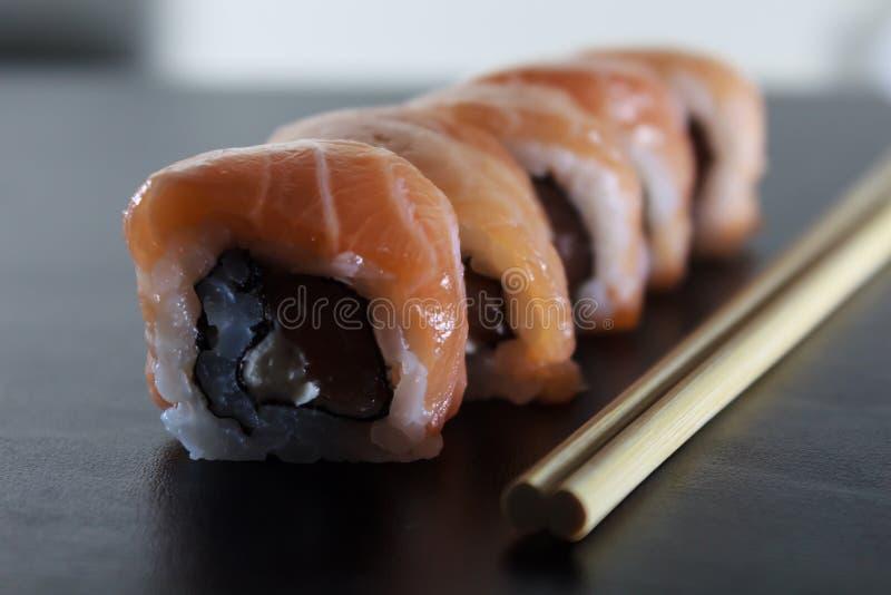 Rollos de sushi frescos deliciosos con los salmones y el queso cremoso en la placa negra Comida japonesa tradicional, concepto sa fotos de archivo