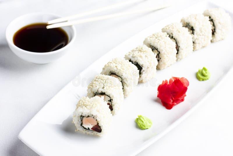 Rollos de sushi japoneses con los salmones en arroz y sésamo en la placa blanca foto de archivo libre de regalías