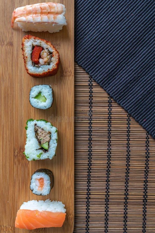 Rollos de sushi de los pescados frescos en el tablero y las esteras de bambú imagen de archivo