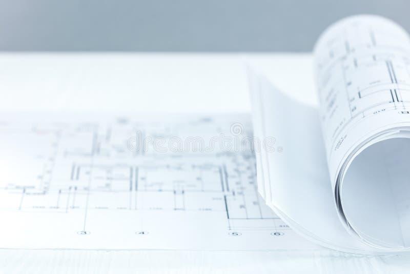 Rollos del modelo y dibujos técnicos en el escritorio workpl del arquitecto fotos de archivo