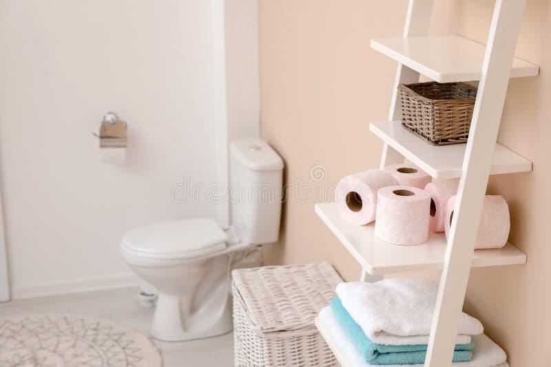 Rollos del papel higiénico en unidad que deja de lado en cuarto de baño fotos de archivo