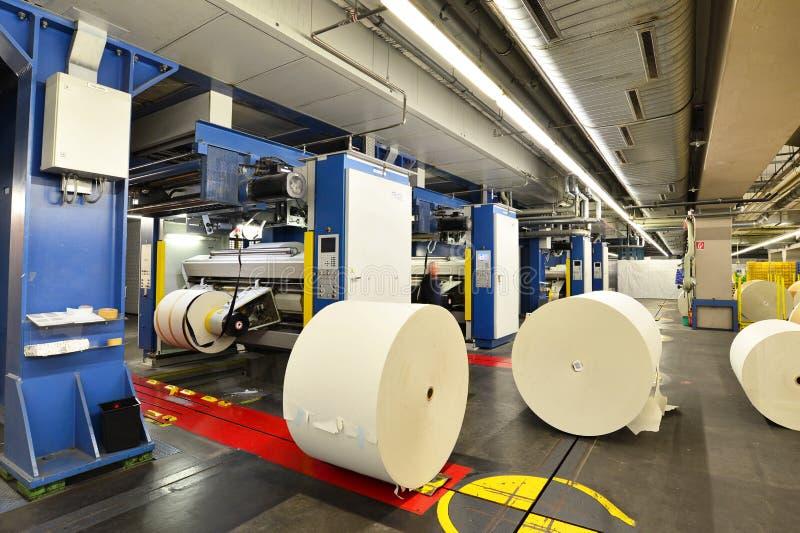 Rollos del papel y máquinas de impresión en offset en una imprenta grande f foto de archivo libre de regalías