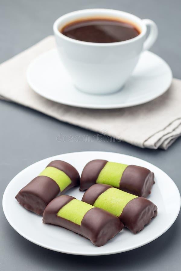 Rollos del punsch de los dulces o punschrullar suecos, cubierto con mazap?n verde, en la placa blanca, servida con el caf?, verti imagenes de archivo