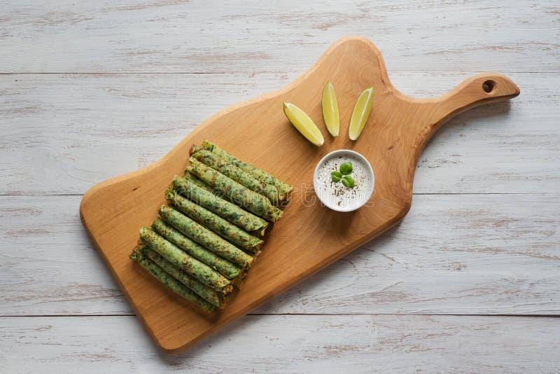 Rollos del verde de la crepe Crepes libres de la espinaca del gluten fotos de archivo