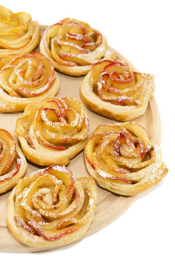 Rollos dulces con las manzanas bajo la forma de rosas en el tablero de madera encendido imágenes de archivo libres de regalías
