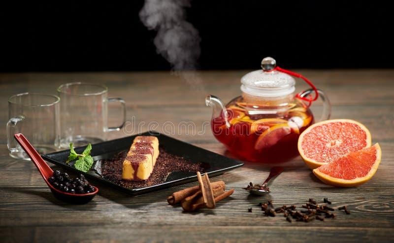 Rollos dulces en placa negra con la puntilla de la salsa y de la menta Tetera por completo de té caliente de la fruta cítrica que foto de archivo libre de regalías