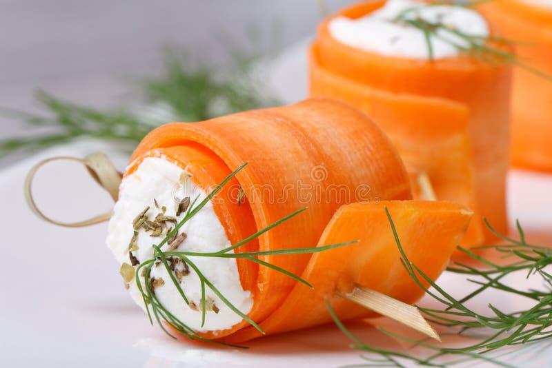 Rollos gastrónomos de zanahorias jovenes con macro del queso cremoso fotos de archivo