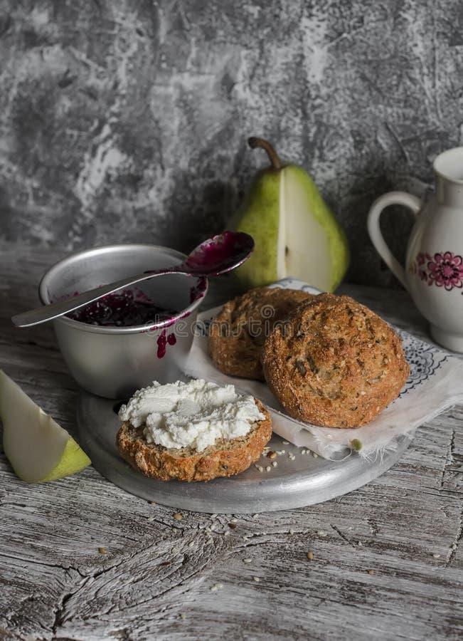 Rollos hechos en casa del trigo integral con queso, atasco del arándano y una pera en un fondo rústico ligero fotografía de archivo