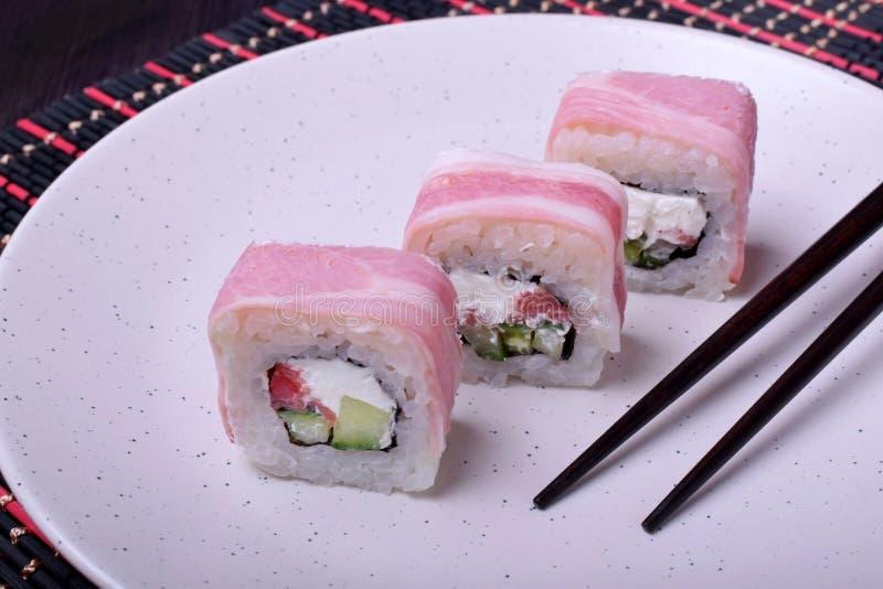 Rollos japoneses con tocino, queso, arroz, los salmones y el pepino en una placa blanca fotografía de archivo