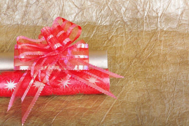 Rolls пестротканой упаковочной бумаги с красным смычком для подарков на предпосылке конспекта золота стоковая фотография rf
